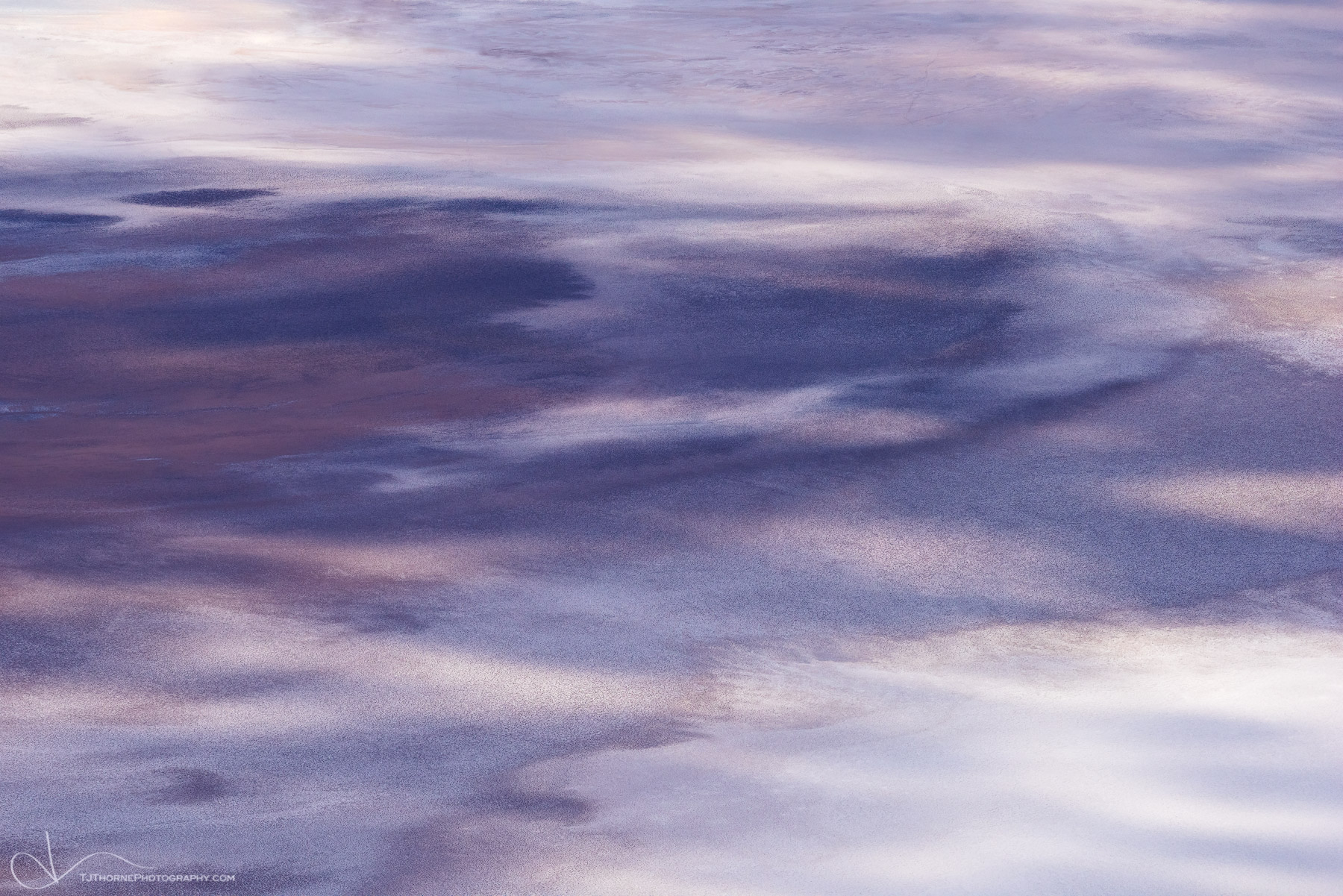 Dappled light moves across the abstract saline patterns of Badwater Basin in Death Valley National Park, California.