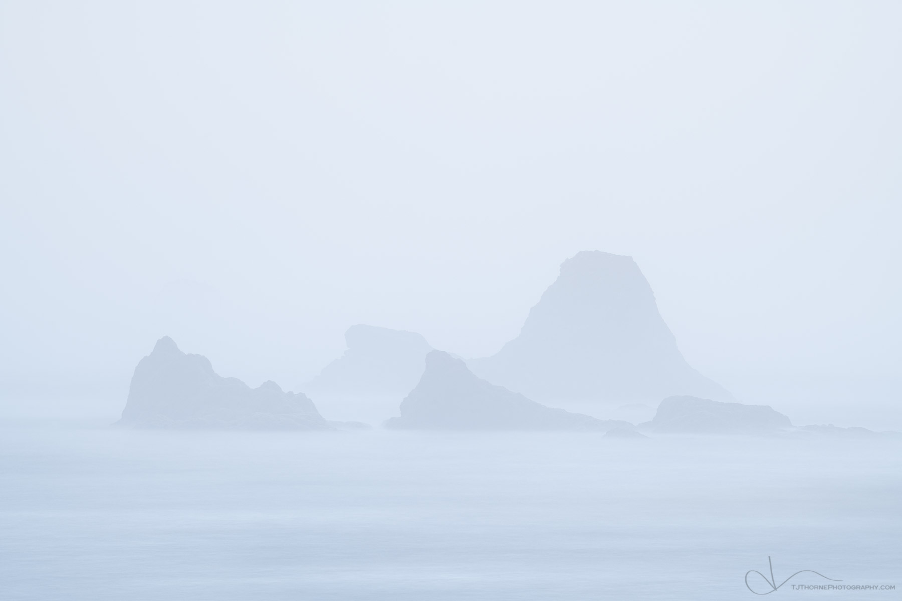 Dense fog obscures off-shore sea stacks near Ruby Beach in Olympic National Park, Washington.